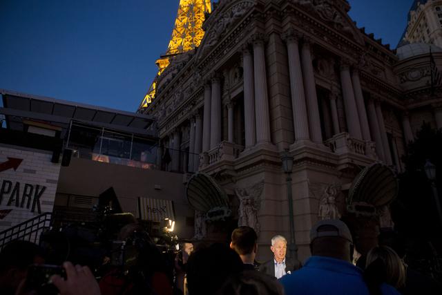 Rich Broome, vicepresidente ejecutivo de Caesars Entertainment Corp., al centro iluminado y en medio de la oscuridad en las afueras del Hotel y Casino Paris Las Vegas, habla en una conferencia de  ...