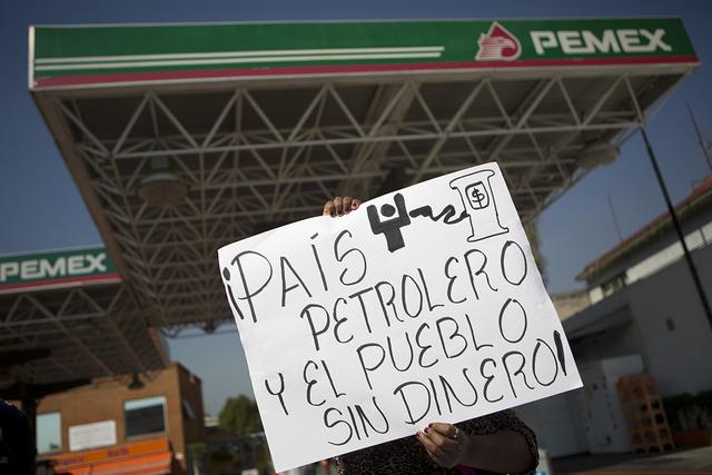 """Una mujer con una pancarta que representa a una persona con una bomba de gasolina, con el mensaje en español: """"El país petrolero y la gente sin dinero"""", protesta el alza de los precios del combu ..."""