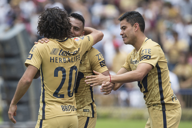 Pumas' Javier Cortes, center, celebrates with Matias Britos, left and Pablo Barrera, after scoring against Leon during a Mexican soccer league match in Mexico City, Sunday, July 31, 2016. (AP Phot ...