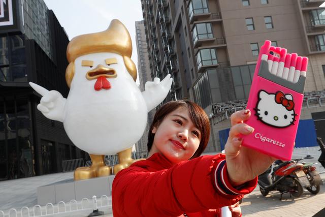 El 30 de diciembre del 2016 una mujer se toma una selfie junto a la escultura de un pollo gigante con rasgos del ahora presidente Donald Trump, afuera de un centro comercial en Taiyuan, Provincia  ...