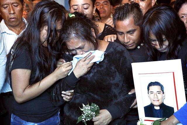 En esta foto del miércoles 21, de septiembre de 2016, las hermanas, sobrinos del sacerdote asesinado José Alfredo Suárez de la Cruz, miran su ataúd inferior en el suelo dentro de la Iglesia de ...