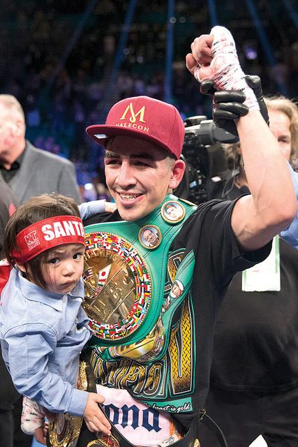 Leo Santa Cruz, sostiene a su hijo Alan, mientras celebra su victoria por decisión dividida contra Carl Frampton en la pelea del campeonato de peso pluma de la AMB en MGM Grand Garden Arena, el s ...