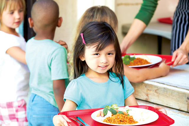 Elementary Pupils Collecting Healthy Lunch In Cafeteria Holding Red Tray Smiling At Camera