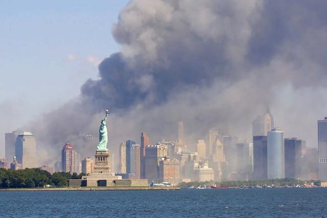 La Estatua de la Libertad en medio del humo que se esparce desde el World Trade Center en New York, el martes 11 de septiembre, 2001 luego del atentado terrorista en que dos aviones arremetieron c ...
