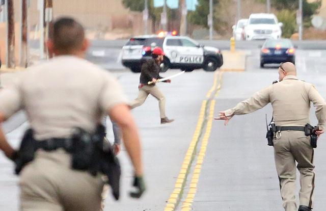 Oficiales de la Policía Metropolitana persiguen a un sujeto armado con una espada samurai, en la calle Gilespie, cerca de East Silverado Ranch Boulevard el lunes 9 de enero del 2017, en Las Vegas ...
