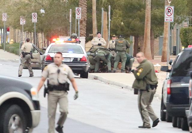 Al fondo se ve a oficiales de policía sometiendo a un hombre armado con una espada samurai, que antes estuvo atrincherado en una casa de la calle Gilespie, cerca de East Silverado Ranch Boulevard ...