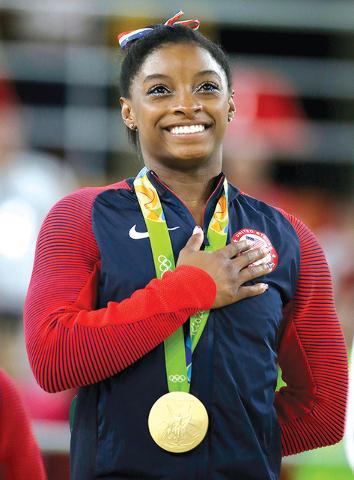 La joven gimnasta Simone Biles ganó oro por su participación en piso. Aquí escucha el himno nacional. el pasado 16 de  Agosto. | Foto AP /Rebecca Blackwell.