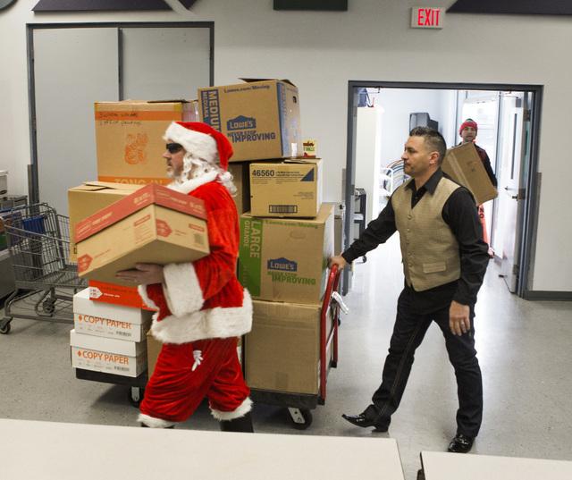 Dave Gildersleeve, vestido como Santa Claus, y su asistente Miguel Hernandez llegan con cajas de juguetes a la Whitney Elementary School el jueves 15 de diciembre del 2016. Empleados de Station Ca ...