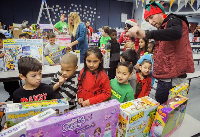 Zane Iorio, con gorro, es empleado de Station Casinos pero aquí aparece como asistente de Santa, ayudando a alumnos de la escuela primaria Whitney a elegir juguetes de regalo, el 15 de diciembre  ...