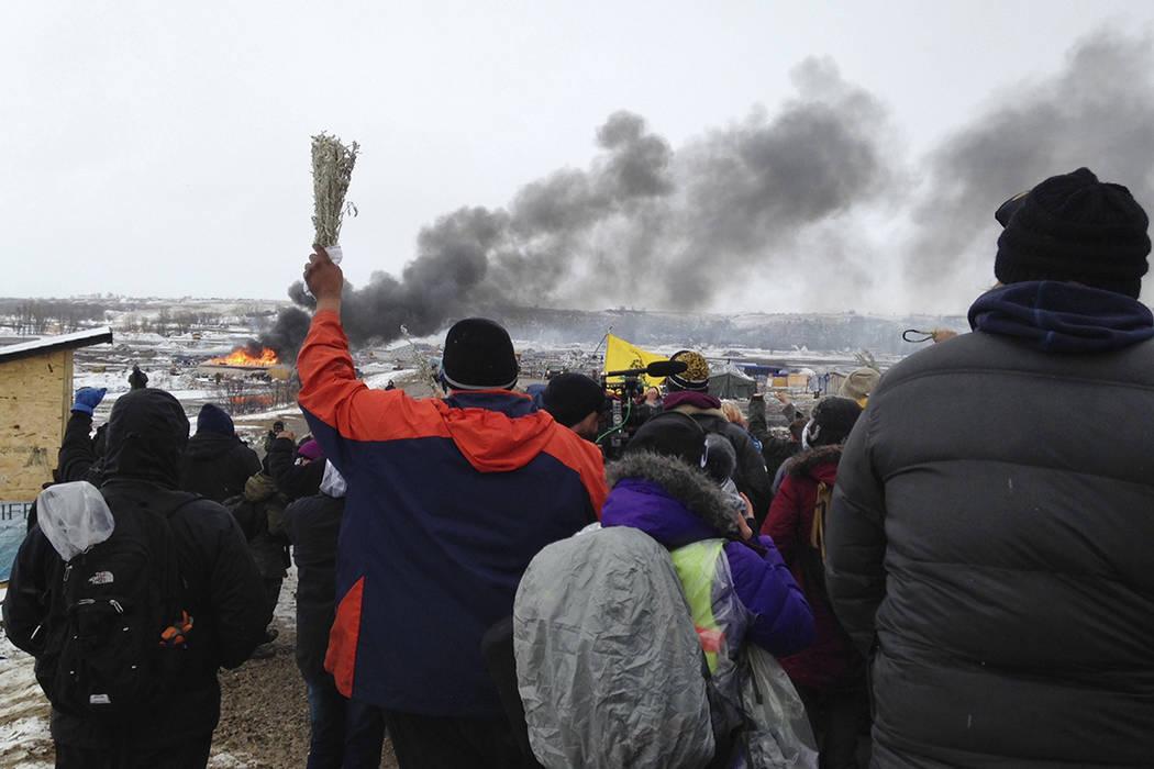 Un incendio arde en el fondo mientras los opositores al oleoducto Dakota Access abandonan su principal campo de protesta el miércoles, 22 de febrero de 2017, cerca de Cannon Ball, N.D., mientras  ...