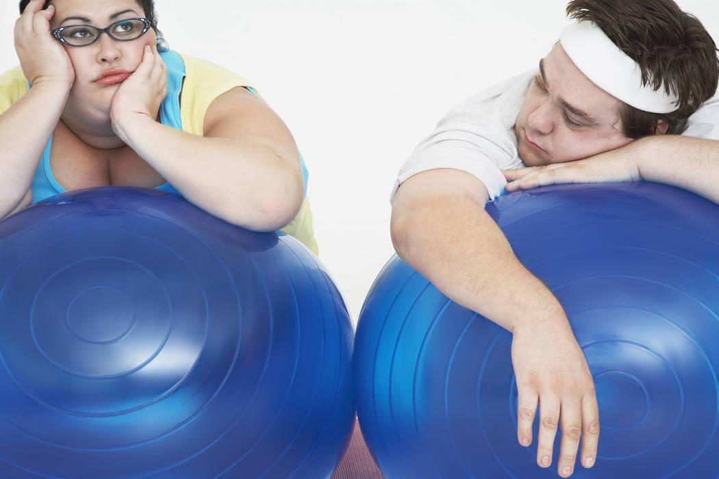 """Una pareja en sobrepeso se relaja sobre las pelotas de ejercicio en el gym. Su pereza puede ser falta de """"Dopamina"""", según estudian los científicos. (Agencias)."""