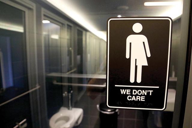 Este símbolo en un baño público es visto afuera de un baño en 21c Museum Hotel en Durham, N.C. Diez estados denunciaron al gobierno federal el viernes 8 de julio, 2016 sobre la directriz requi ...