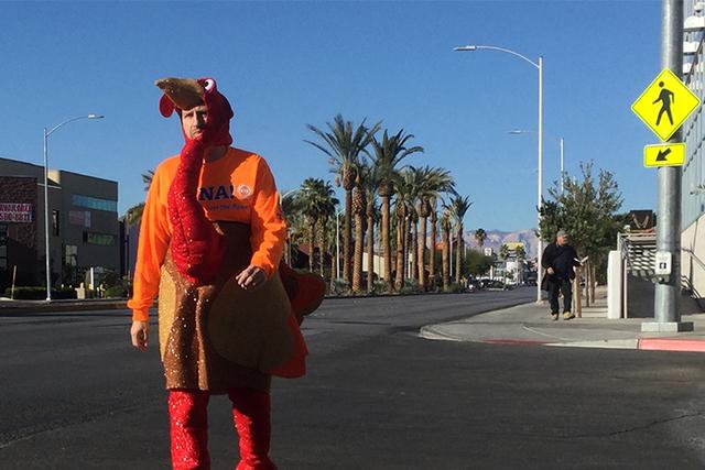 """El senador Mark Manendo, D-Las Vegas, en un disfraz de """"pavo"""" camina en un cruce del boulevard E. Charleston, mientras agentes de la policía vigilan en un operativo el martes 22 de noviembre del  ..."""