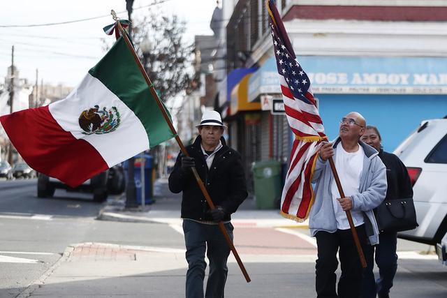 Los miembros de la Asociación Mexicana de Perth Amboy, izq., Rodolfo Cortes, Leonardo Sánchez y Alicia Ireneo llevan banderas mientras participan en una protesta de inmigración, el jueves 16 de ...