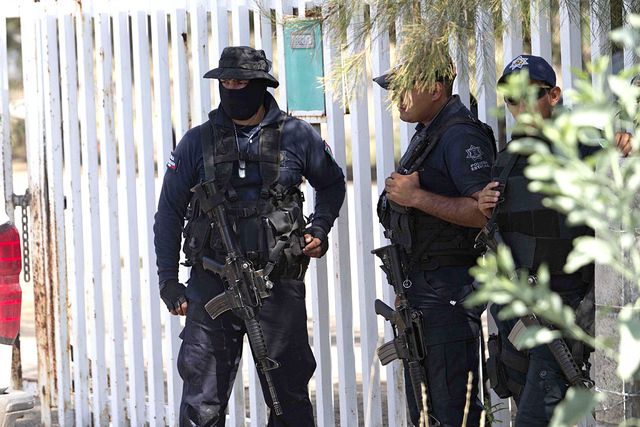 Policía del estado de Michoacán hacen guardia cerca de la entrada del Rancho del Sol, cerca de Vista Hermosa, México, el viernes, 22 de mayo de 2015. | Foto AP / Refugio Ruiz