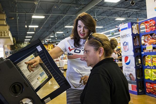 Maritza Rodríguez, izq. coordinadora de área para Mi Familia Vota, muestra a María Sánchez cómo utilizar la máquina de votación en un día de elecciones, el lunes 15 de agosto de 2016 en La ...