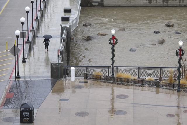 Una mujer camina bajo la lluvia en el centro de Reno, Nevada, el 4 de enero del 2017, en un puente del rio Truckee. Han subido los niveles de las aguas por lluvias y mal tiempo, que han causado al ...