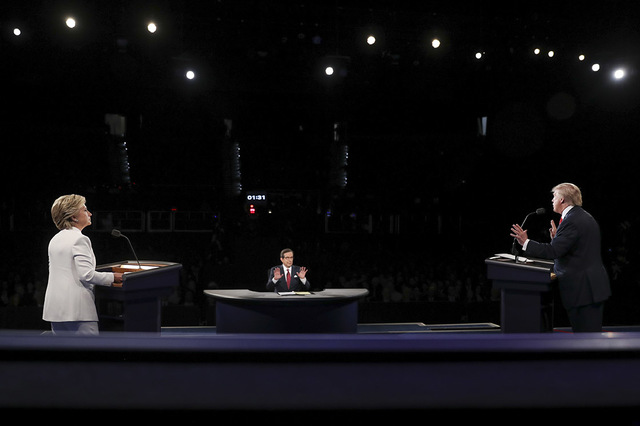 La demócrata nominada a la presidencia, Hillary Clinton (izquierda), escucha al su oponente republicano Donald Trump responder una pregunta del moderator Chris Wallace durante el tercero y últim ...