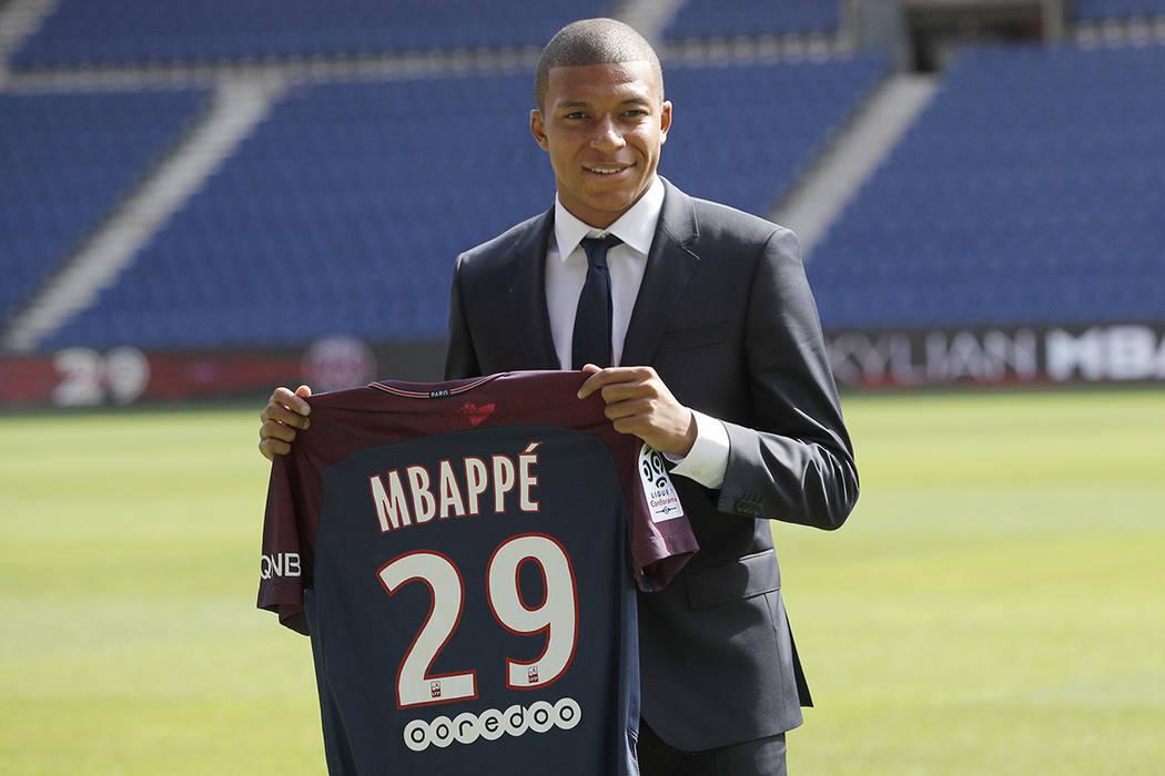"""El jugador de fútbol francés Kylian Mbappe posa con su camisa de equipo tras una rueda de prensa en París, el miércoles 6 de septiembre de 2017. Mbappe es un joven muy apresurado y quiere """"gan ..."""