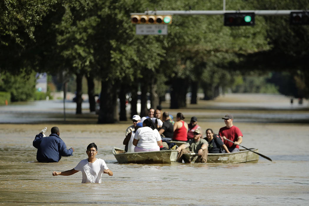 Gente evacua un vecindario inundado después de que el agua fuera liberada del cercano embalse de Addicks cuando alcanzó su capacidad debido a la tormenta tropical Harvey. Miércoles 30 de agosto ...