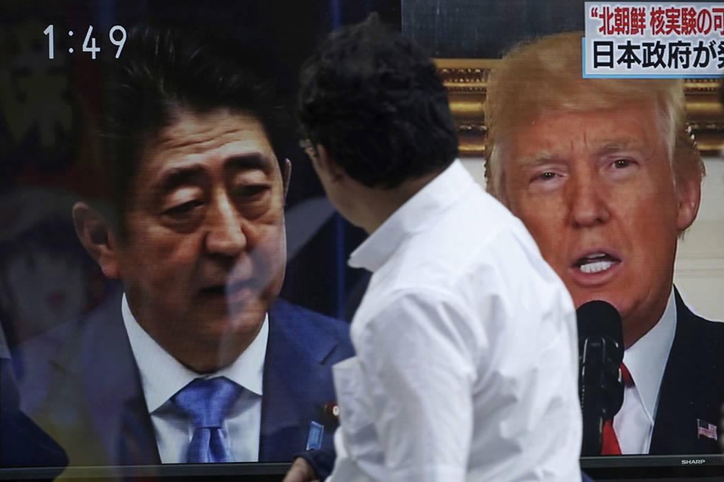 Un hombre pasa por delante de una noticia en la televisión que muestra las imágenes del primer ministro japonés, Shinzo Abe, a la izquierda, y el presidente de Estados Unidos, Donald Trump, a l ...