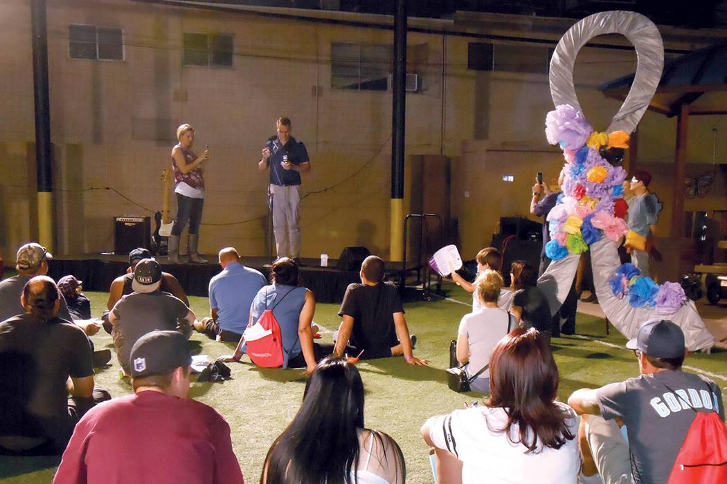 A la derecha arriba se ve un listón plateado gigante, símbolo de la lucha contra la muerte por abuso de opioides, mientras gente sentada escucha qué hacer para ayudar a una víctima de sobredos ...
