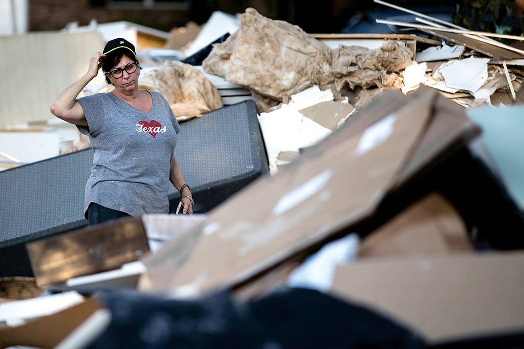 Sherri Blatt se encuentra entre los escombros en frente de su casa, las secuelas del huracán Harvey el miércoles, 6 de septiembre de 2017, en Houston. | Foto de AP / Matt Rourke.