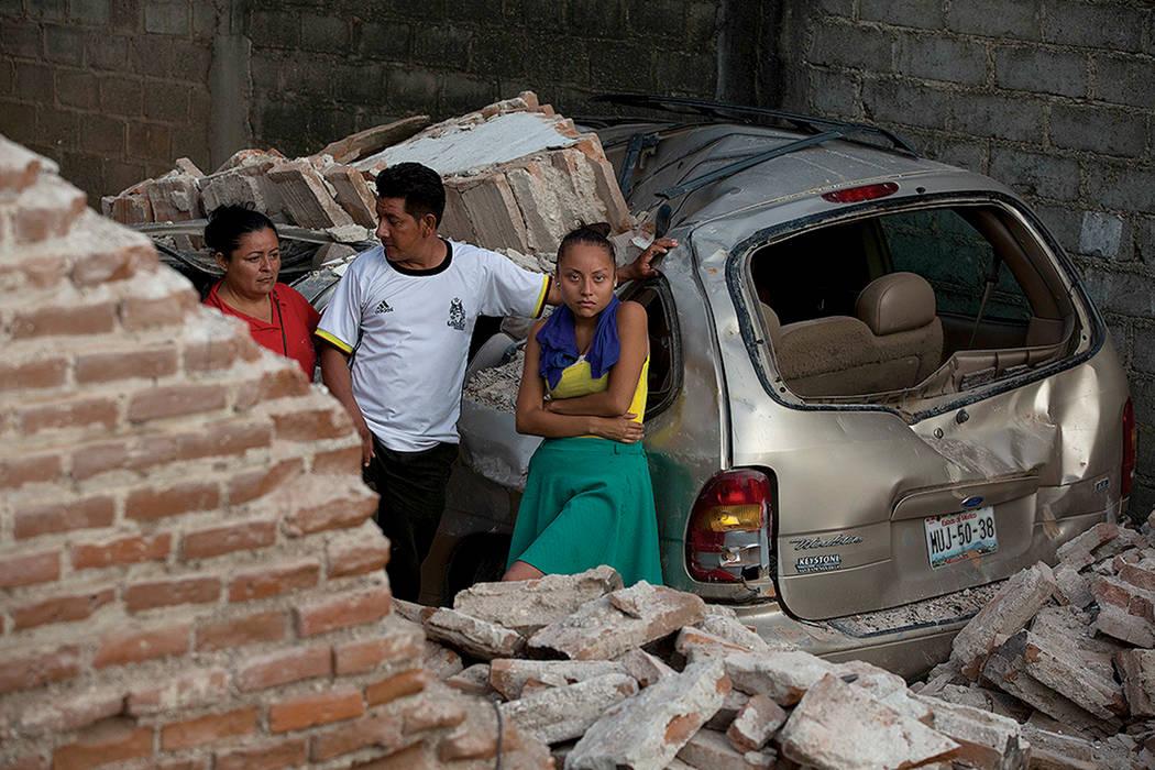 Una familia se encuentra en medio de los escombros del terremoto que dañó su hogar y automóvil en Juchitan, estado de Oaxaca, México, el sábado 9 de septiembre de 2017. Foto Rebecca Blackwell ...