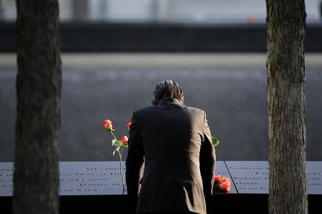 Un hombre está parado en el borde de la cascada en el zona cero durante una ceremonia en el décimosexto aniversario de los ataques del 11 de septiembre en Nueva York, lunes, 11 de septiembre de  ...