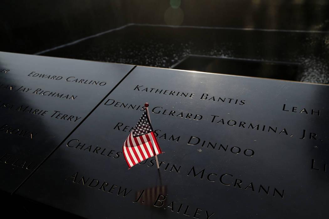 Una bandera estadounidense se alza sobre los nombres de las víctimas de los ataques terroristas del 11 de septiembre, antes de una ceremonia en la zona cero en Nueva York, el lunes, 11 de septiem ...