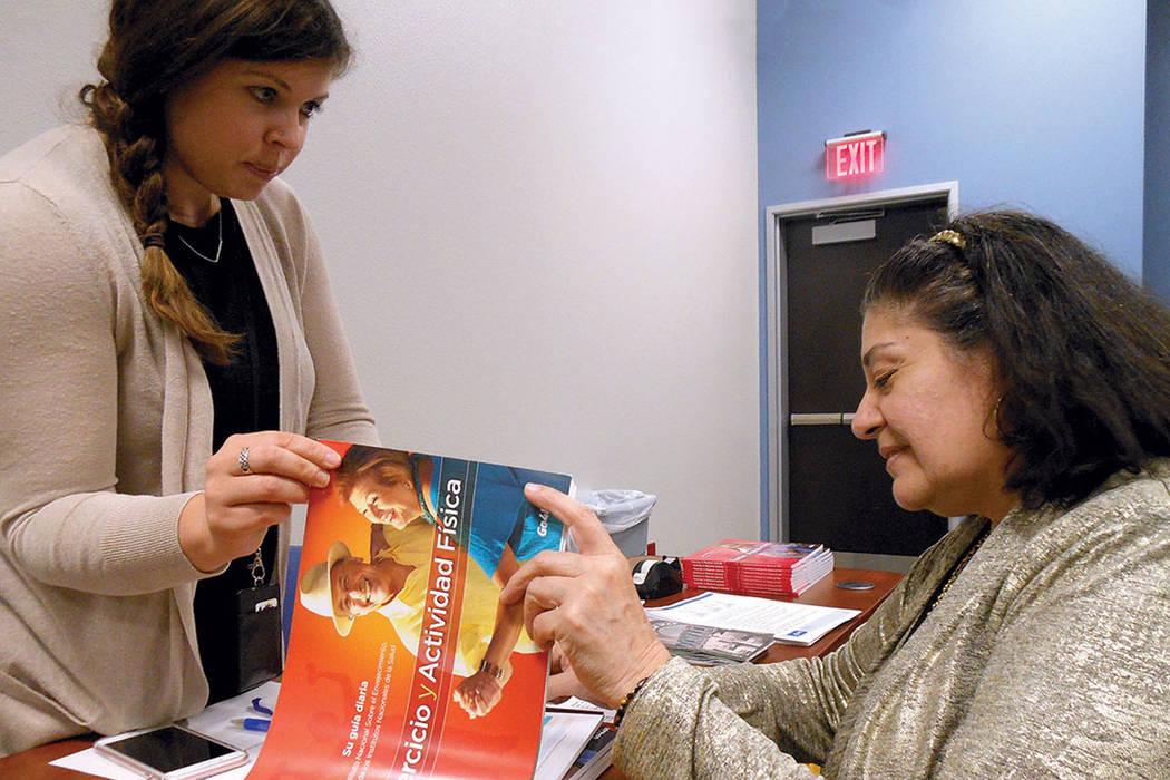 """2. La educadora de salud, del SNHD, Jessica Johnson (izquierda) muestra el contenido del libro """"Ejercicio y actividad física"""" a Ana Conroy, en el inicio de la """"Semana de Prevención de Caí ..."""