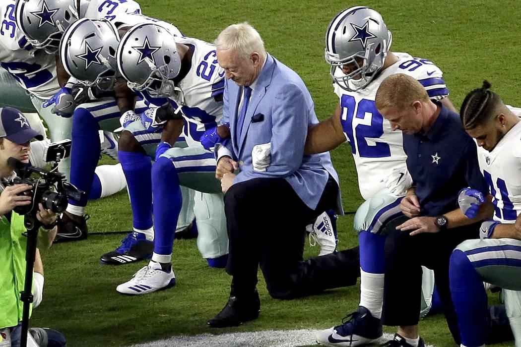 Los Dallas Cowboys, encabezados por el dueño Jerry Jones, centro, toman una rodilla antes del himno nacional previo a un partido de fútbol de la NFL contra los Cardenales de Arizona, el lunes 25 ...
