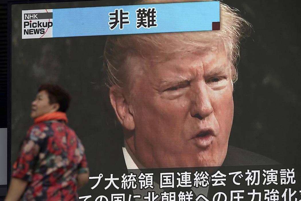 Una mujer pasa por una pantalla de televisión mostrando al presidente estadounidense, Donald Trump, mientras informa sobre su discurso de inauguración en la Asamblea General de la ONU, en Tokio, ...