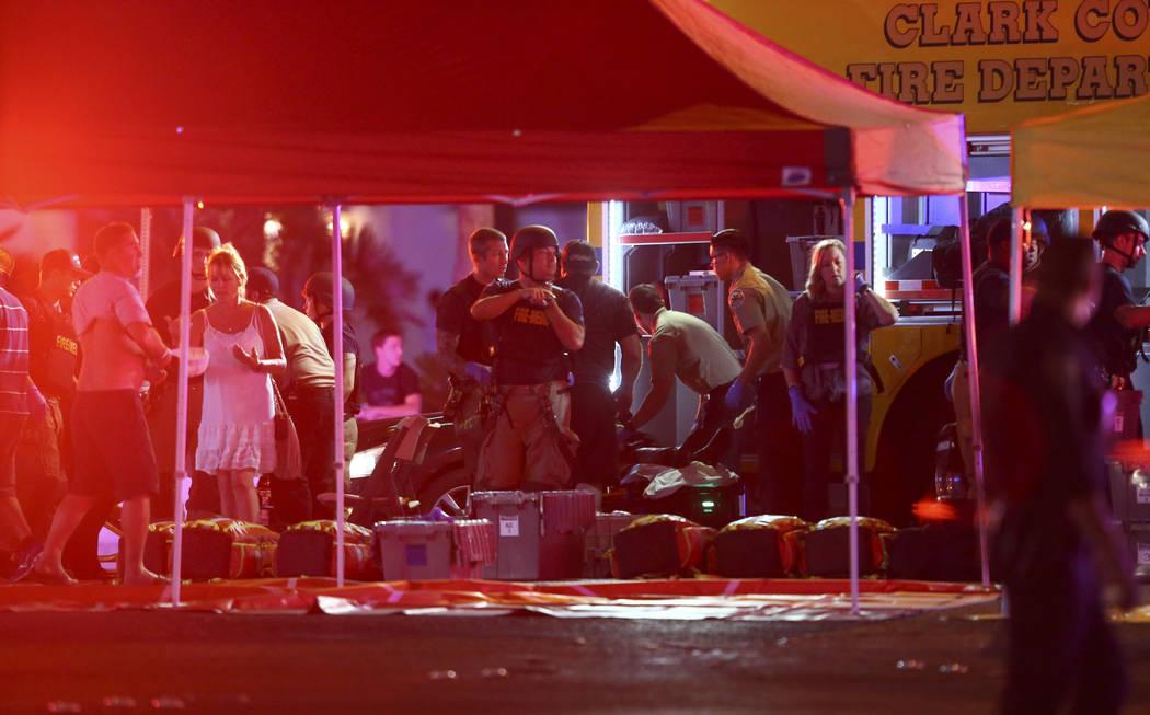Los médicos tratan a los heridos mientras la policía de Las Vegas responde durante una situación de disparos activos en el Strip de Las Vegas en Las Vegas el domingo 1 de octubre de 2017. Chase ...