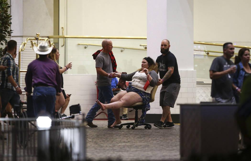 Una mujer herida se traslada fuera del Tropicana durante una situación de tirador activo en el Strip de Las Vegas en Las Vegas el domingo 1 de octubre de 2017. (Chase Stevens/Las Vegas Review-Jou ...