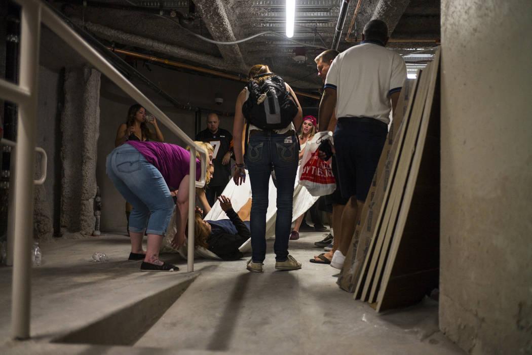 La gente ayuda a una mujer herida en el Tropicana durante una situación activa del francotirador en Las Vegas Strip el domingo, 1 de octubre, 2017. Chase Stevens Las Vegas Review-Journal @cssteve ...