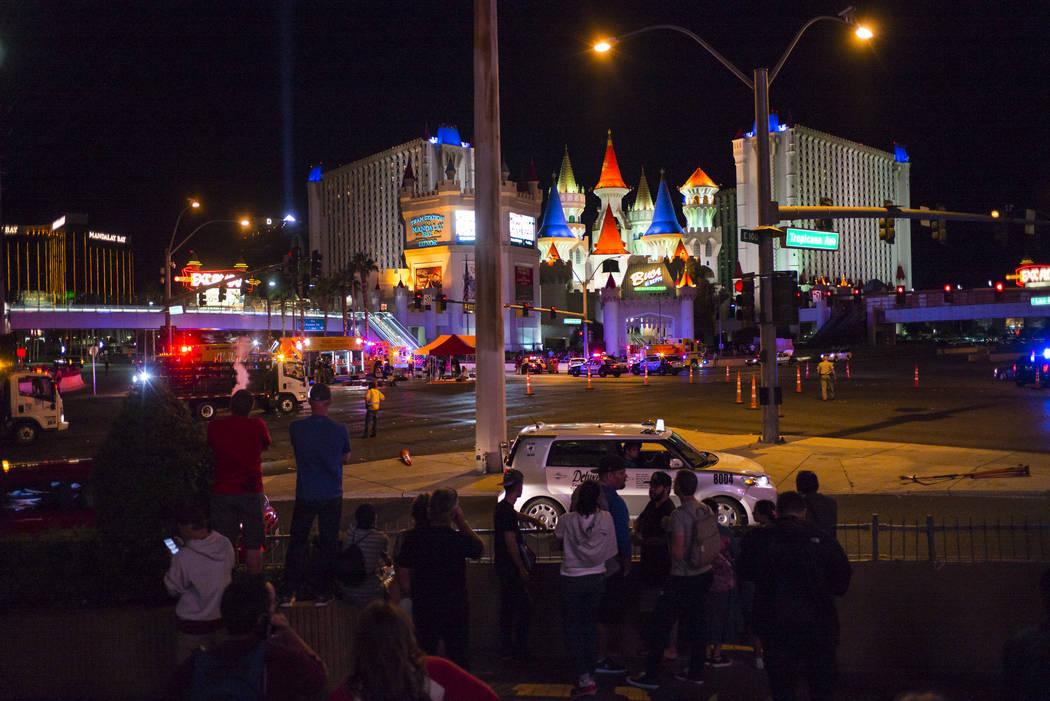 Peatones miran mientras que la policía de Las Vegas responde durante una situación activa de francotirador en Las Vegas Strip cerca de la avenida de Tropicana en Las Vegas el domingo, 1 de octub ...