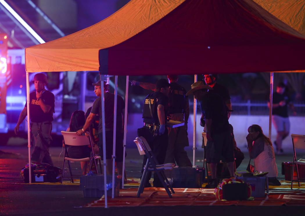Trabajadores de emergencia atienden a los heridos mientras la policía de Las Vegas responde durante una situación de disparos activos en el Strip de Las Vegas el domingo 1 de octubre de 2017. Ch ...