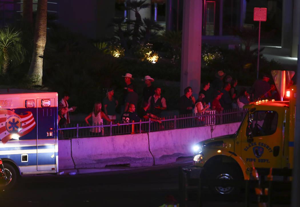 Peatones observan como la policía de Las Vegas responde durante una situación de francotirador activo en el Strip de Las Vegas cerca de Tropicana Avenue en Las Vegas el domingo 1 de octubre de 2 ...