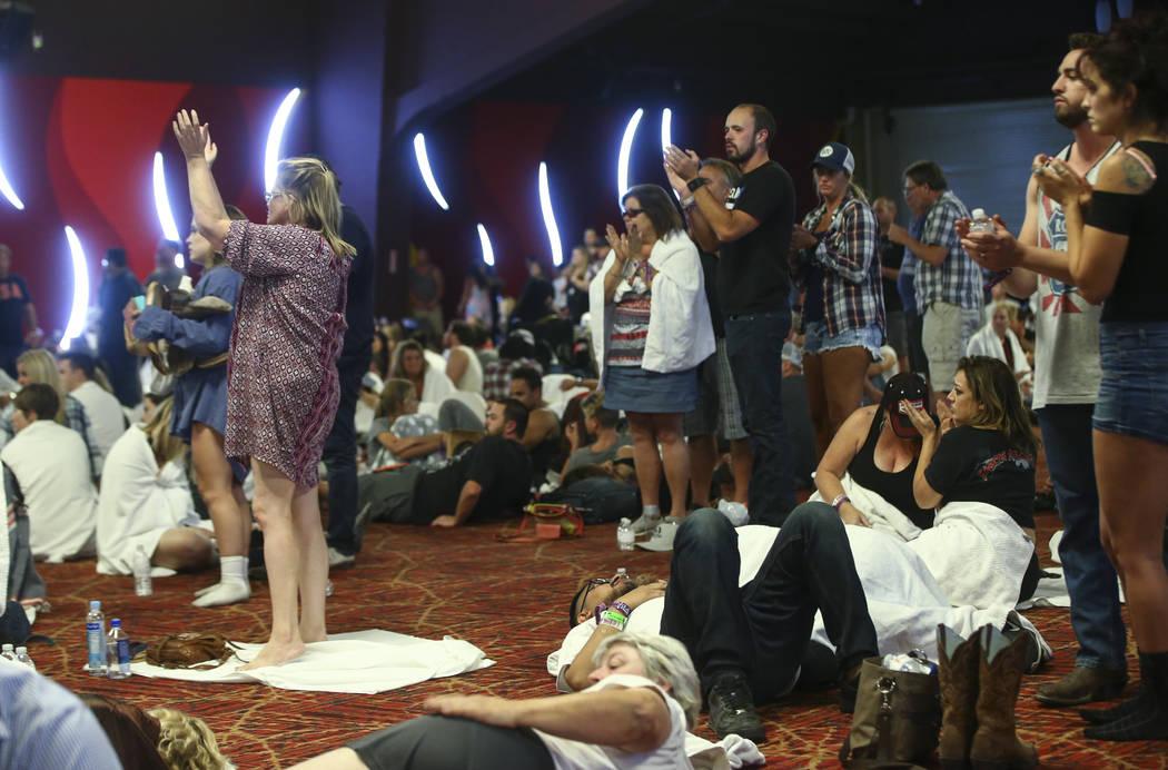 La gente aplaude después de ser actualizado por un oficial de policía de Las Vegas durante el cierre en el Tropicana Las Vegas después de una situación de disparos activos que dejó 50 muertos ...