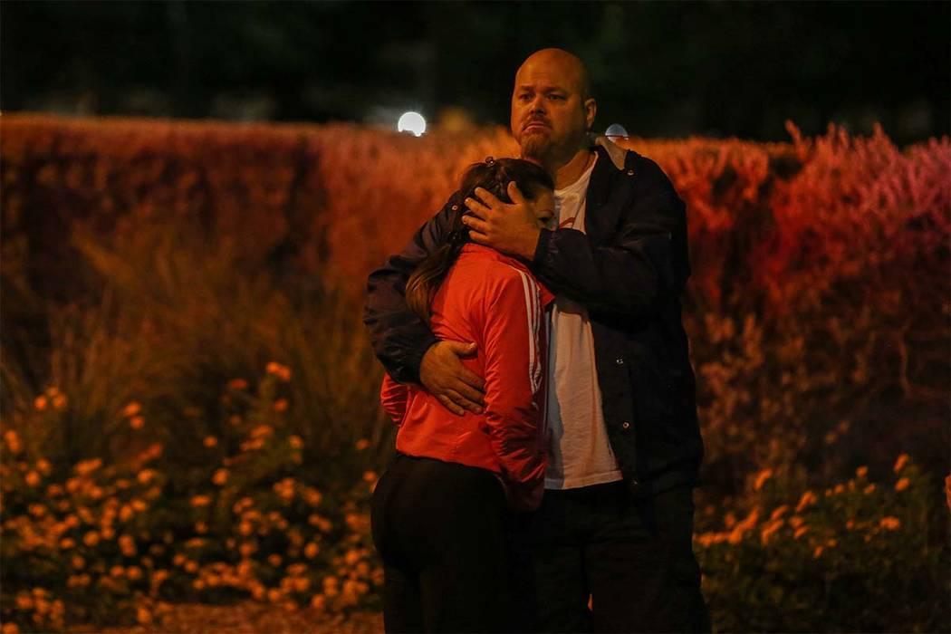 Un hombre y una mujer se abrazan fuera del cuartel general del Departamento de Policía Metropolitana de Las Vegas en Las Vegas, el domingo, 1 de octubre de 2017. LVMPD preguntó si alguien tenía ...