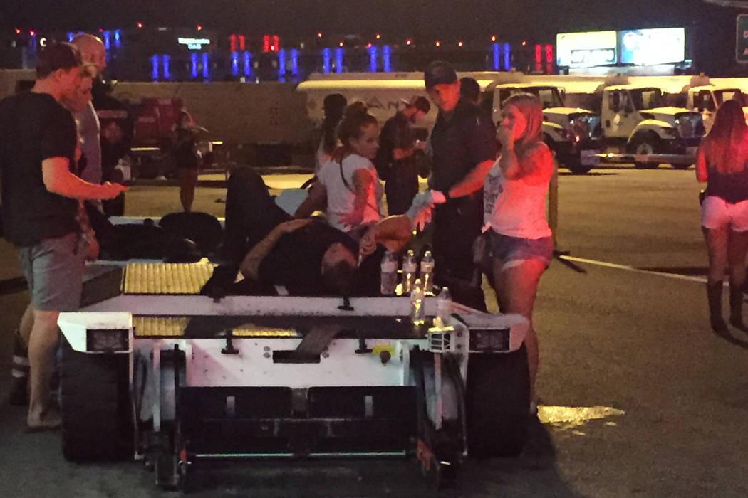 Un hombre espera una ambulancia en la terminal ejecutiva del Aeropuerto Internacional McCarran después de haber sido disparado durante una situación activa de francotirador en el Strip de Las Ve ...