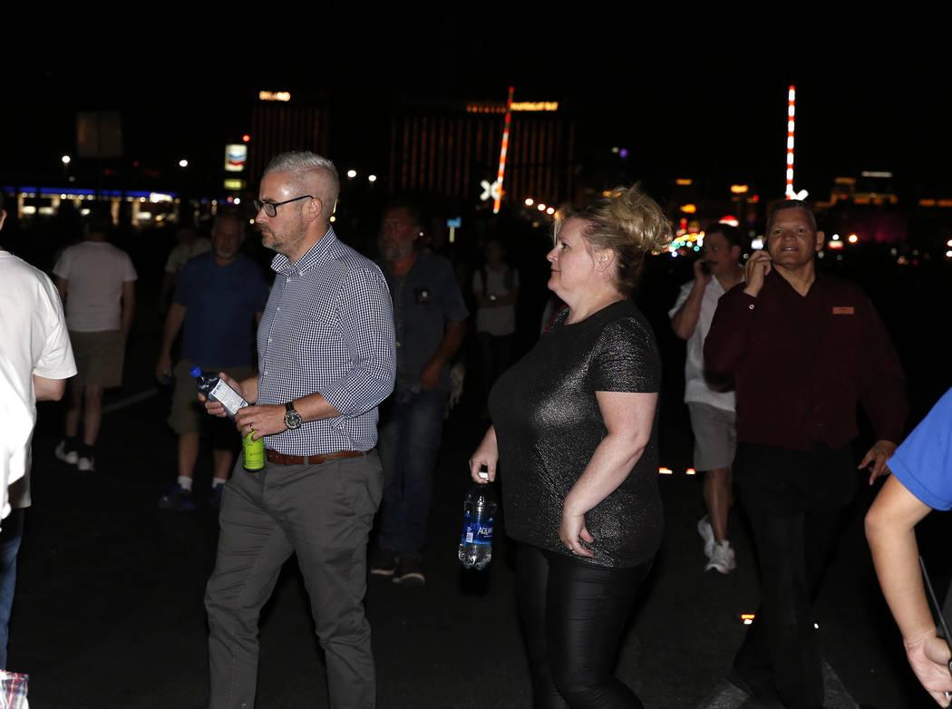 Las personas que han sido evacuadas del Mandalay Bay hotel-casino caminan en Las Vegas Boulevard mientras la policía de Las Vegas responde durante una situación activa de francotirador en el Str ...