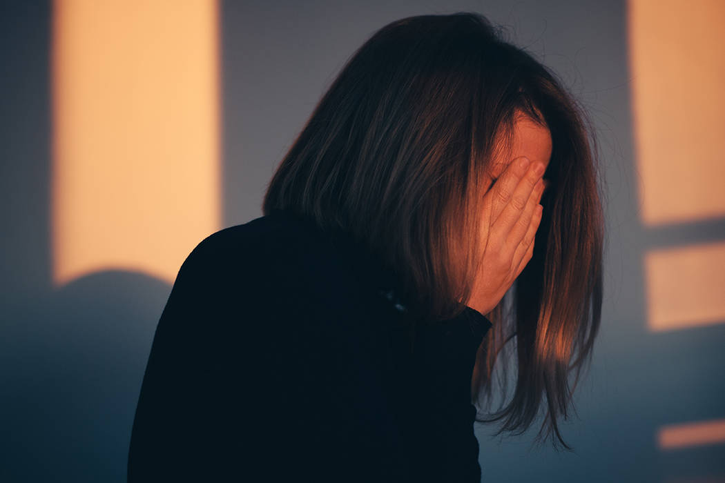 A woman sitting alone and depressed in window light