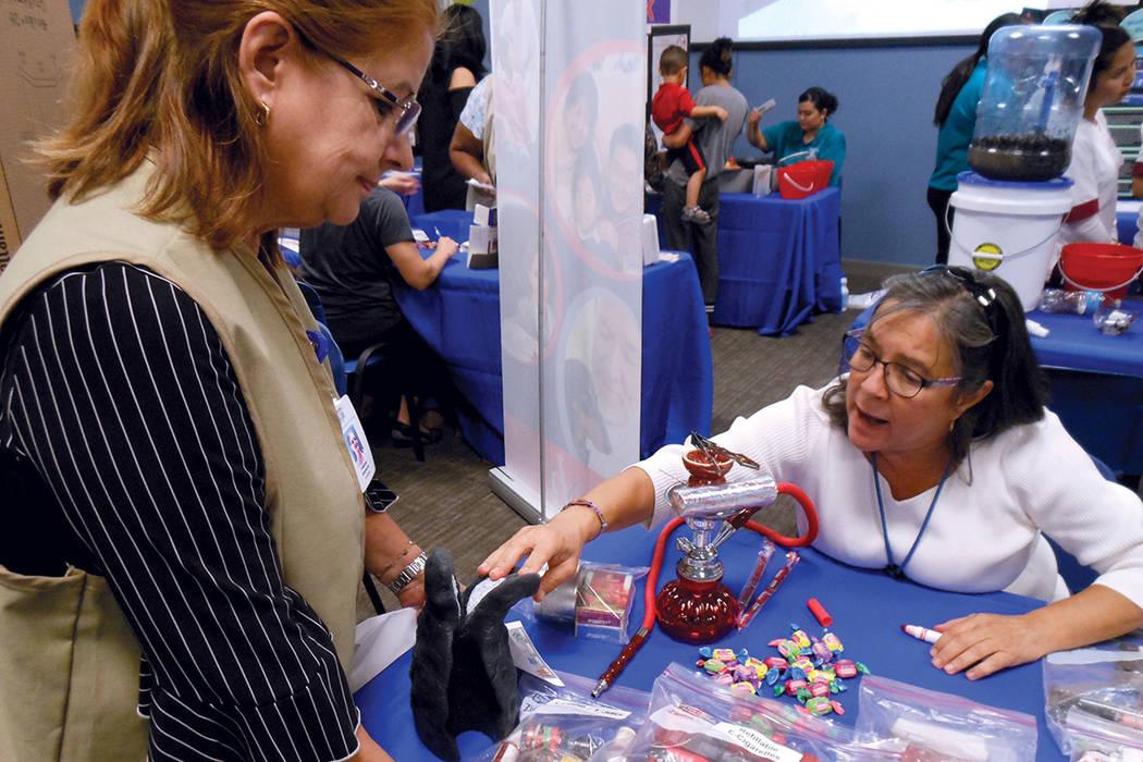 """En el puesto de """"Vival libre de tabaco"""" la educadora de salud Gail Muñiz (derecha) explica a Virginia González cómo se ponen los pulmones de un fumador.   Fotos Valdemar González/ El Tiempo."""
