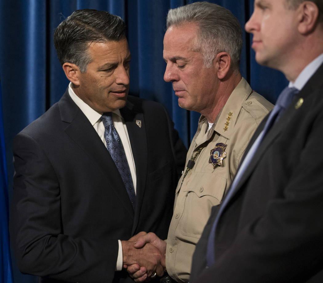 El Gobernador Brian Sandoval, a la izquierda, y el Sheriff del Condado de Clark Joe Lombardo durante una conferencia de prensa sobre el tiroteo masivo, en el cuartel general del Departamento de Po ...