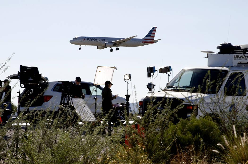 Un avión de American Airways vuela por encima de camiones televisión por satélite cerca del Aeropuerto Internacional McCarran el lunes 2 de octubre de 2017 en Las Vegas. Bizuayehu Tesfaye Las V ...