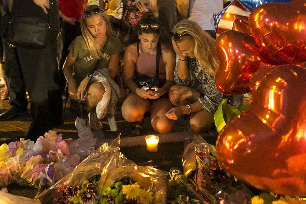 Las personas visitan un monumento improvisado para las víctimas del tiroteo masivo del  Festival de la Ruta 91 que está situado en Las Vegas Boulevard  y Reno Avenue en Las Vegas, el martes 3 de ...
