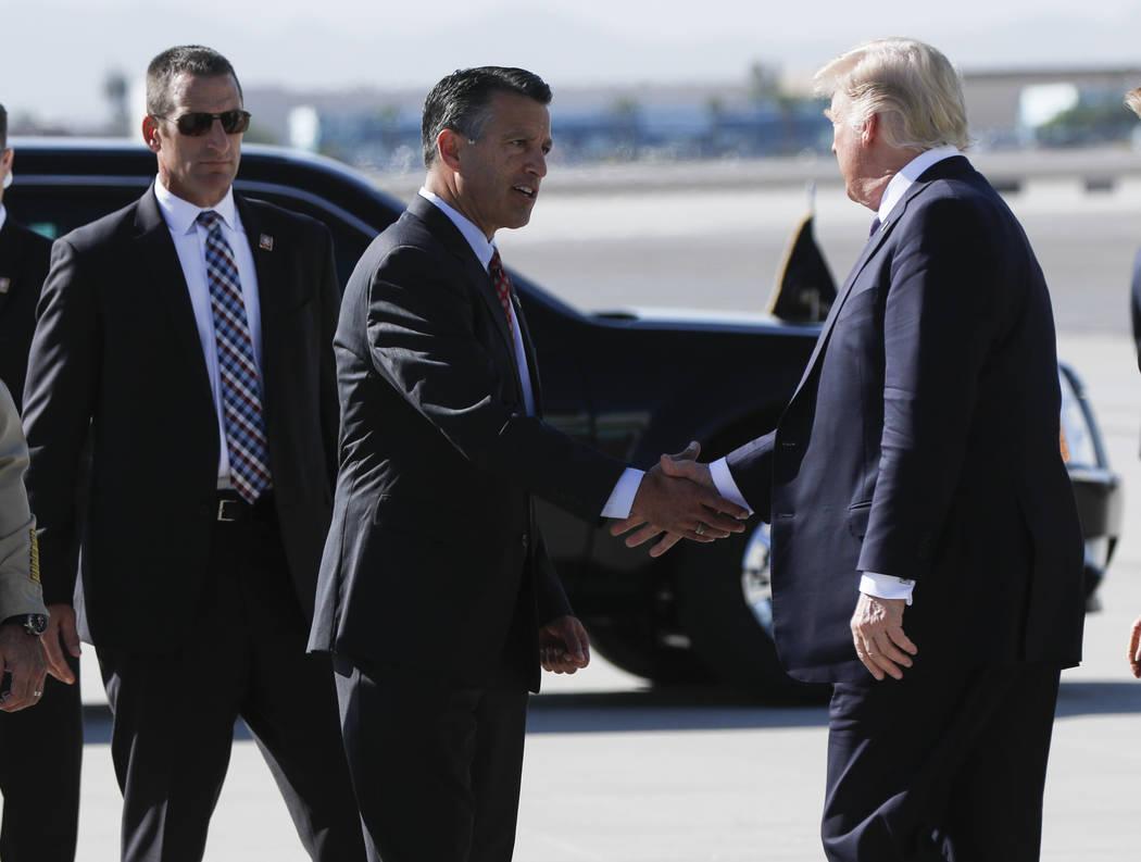 El gobernador Brian Sandoval saluda al presidente Donald Trump a su llegada al aeropuerto internacional de McCarran en Las Vegas el miércoles 4 de octubre de 2017. Un pistolero abrió fuego contr ...