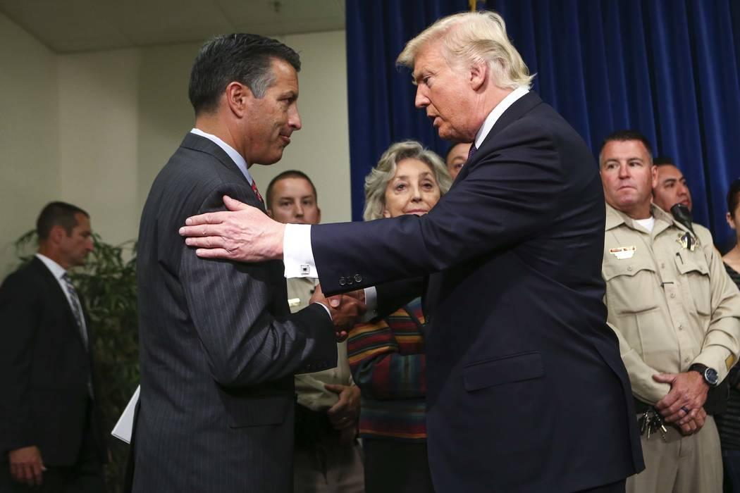 El presidente Donald Trump abraza al gobernador de Nevada Brian Sandoval en el cuartel general del Departamento de Policía Metropolitana en Las Vegas el miércoles 4 de octubre de 2017. Un pistol ...